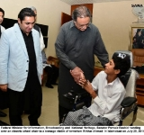 Federal Minister for Information, Broadcasting and  National Heritage, Senator Pervaiz Rashid handing over an electric wheel chair to a teenage victim of terrorism Iftikhar Ahmad  in Islamabad on July 25, 2014