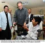Federal Minister for Information, Broadcasting and  National Heritage, Senator Pervaiz Rashid handing over an laptop to a teenage victim of terrorism Iftikhar Ahmad  in Islamabad on July 25, 2014