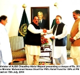 Prime Minister of AJ&K Chaudhry Abdul Majeed presenting a cheque of Rs. 20 Million to Prime Minister Muhammad Nawaz Sharif for PM's Relief Fund for IDPs at PM House Islamabad on 15th July, 2014