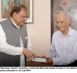President Mamnoon Hussain receiving a book from Mushtaq Ahmed Yousufi at his residence in the metropolis at Karachi on 22 July 2014